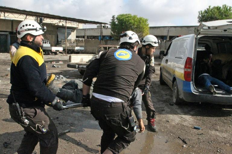 Members of the Syrian Civil Defence, or White Helmets, evacuate a victim following a regime air strike