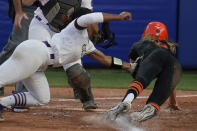 Oklahoma State's Scotland David, right, is tagged out at home plate by James Madison pitcher Odicci Alexander, left, in the seventh inning of a Women's College World Series softball game, Friday, June 4, 2021, in Oklahoma City. (AP Photo/Sue Ogrocki)