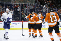 Philadelphia Flyers' Scott Laughton (21) celebrates with Ivan Provorov (9) and Kevin Hayes (13) after scoring a goal as Toronto Maple Leafs' Justin Holl (3) skates by during the second period of an NHL hockey game, Tuesday, Dec. 3, 2019, in Philadelphia. (AP Photo/Matt Slocum)