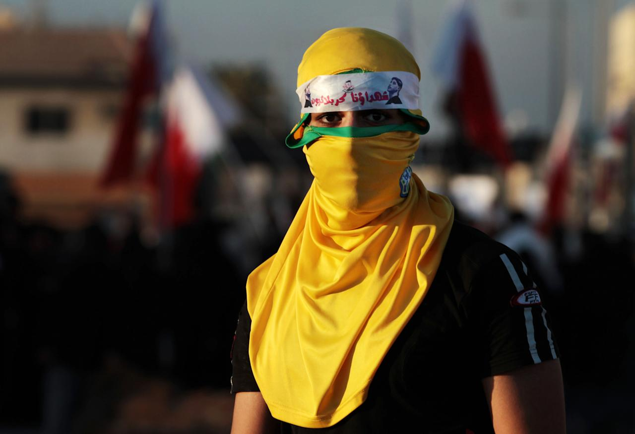 "A masked Bahraini anti-government protester looks for riot police in front of a march in Malkiya village, Bahrain, Tuesday, Dec. 4, 2012. His headband in Arabic reads, ""our martyrs are Karbalais,"" referring to the battle of Karbala, in Iraq, centuries ago. (AP Photo/Hasan Jamali)"