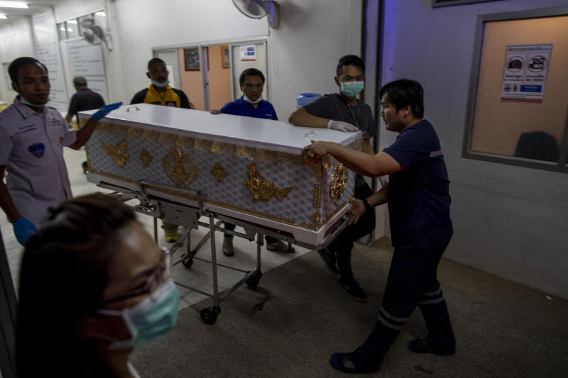 Morgue staff a push a trolley with a coffin at a morgue, Korat, Nakhon Ratchasima, Thailand, Sunday, Feb. 9, 2020. Thai officials say a soldier who went on a shooting rampage and killed numerous people and injured dozens of others has been shot dead inside the mall in northeastern Thailand. (AP Photo/Gemunu Amarasinghe)