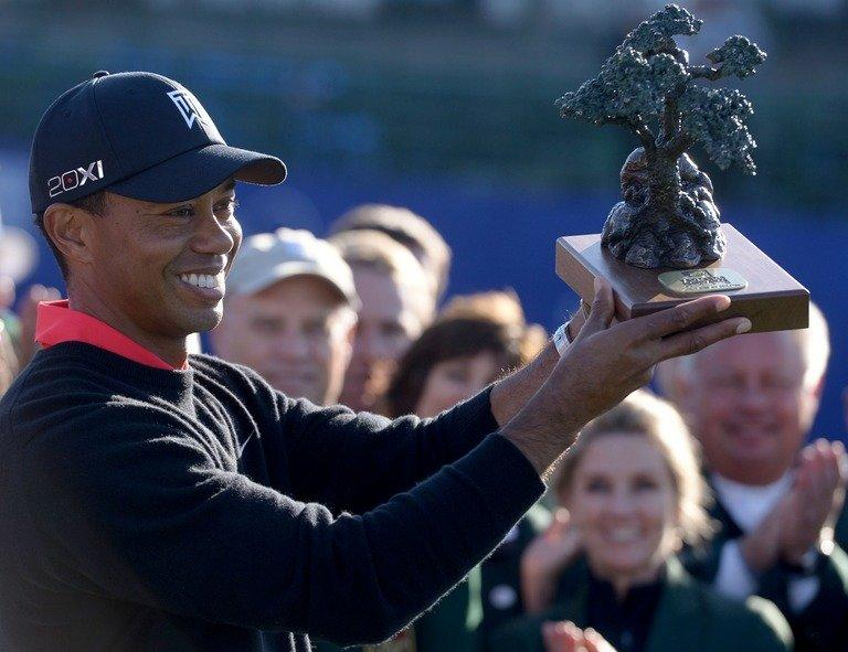 Tiger Woods holds the winner's trophy after victory at the Farmers Insurance Open at Torrey Pines on January 28, 2013. Despite struggling in windy conditions Monday, Woods showed flashes of the form that has brought him 14 major titles, four shy of the all-time record of 18 won by Jack Nicklaus