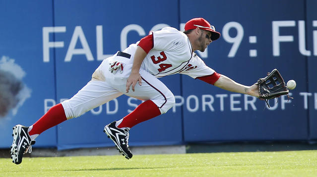 Washington Nationals outfielder Bryce Harper is unable to make the catch on a ball hit by Houston Astros' Brian Bixler in the eighth inning of a spring training baseball game, Sunday, March 4, 2012, in Viera, Fla. (AP Photo/Julio Cortez)