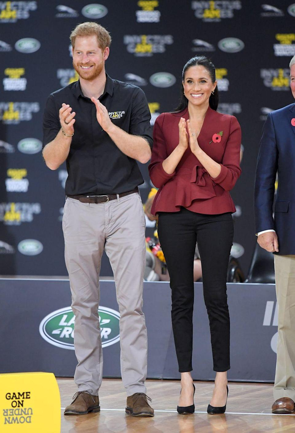 """<p>Harry and Meghan cheered on the Invictus Games wheelchair basketball final at the Quay Centre in Sydney. The Duchess wore <a href=""""https://outlanddenim.com/products/harriet-in-black"""" rel=""""nofollow noopener"""" target=""""_blank"""" data-ylk=""""slk:Outland Denim skinny jeans"""" class=""""link rapid-noclick-resp"""">Outland Denim skinny jeans</a> with a wrap top by Scanlan Theodore. She also wore one of her favorite pairs of heels, the Jay Pump by Sarah Flint.</p><p><a class=""""link rapid-noclick-resp"""" href=""""https://go.redirectingat.com?id=74968X1596630&url=https%3A%2F%2Fwww.sarahflint.com%2Fproducts%2Fjay-pump-85-black-suede&sref=https%3A%2F%2Fwww.townandcountrymag.com%2Fstyle%2Ffashion-trends%2Fg3272%2Fmeghan-markle-preppy-style%2F"""" rel=""""nofollow noopener"""" target=""""_blank"""" data-ylk=""""slk:SHOP NOW"""">SHOP NOW</a> <em>Sarah Flint Jay Pump, $395</em></p>"""