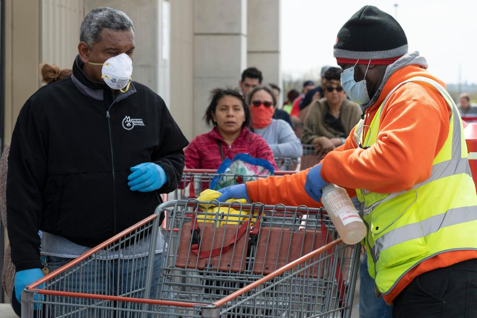 A Costco employee disinfects a shopping cart as shoppers line up to get into the bulk shopping store in Washington, DC, on April 5, 2020. - The number of confirmed coronavirus, COVID-19,  cases in the United States has topped 300,000 and there have been more than 8,100 deaths, Johns Hopkins University reported on Saturday. (Photo by JIM WATSON / AFP) (Photo by JIM WATSON/AFP via Getty Images)