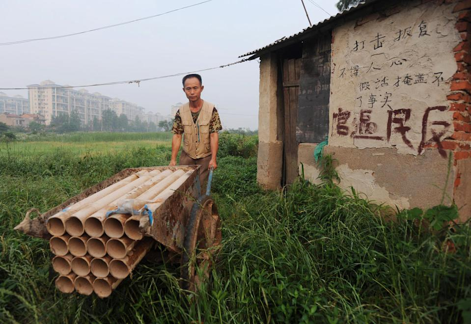 "In a picture taken on June 6, 2010 Chinese farmer Yang Youde shows his homemade cannons on his farmland on the outskirts of Wuhan, in central China's Hubei province. Yang's improvised cannons, which are made out of a wheelbarrow, pipes and fire rockets, are used to defend his fields against property developers who want his land. Land seizures have been a problem for years in China, and have given rise to the term ""nail house"" to describe a holdout tenant or occupant, likening them to a nail refusing to be hammered down. CHINA OUT AFP PHOTO (Photo credit should read STR/AFP via Getty Images)"