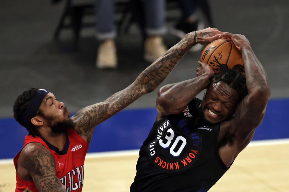 New York Knicks forward Julius Randle, right, battles for the ball with New Orleans Pelicans forward Brandon Ingram, left, during the second half of an NBA basketball game Sunday, April 18, 2021, in New York. (AP Photo/Adam Hunger, Pool)