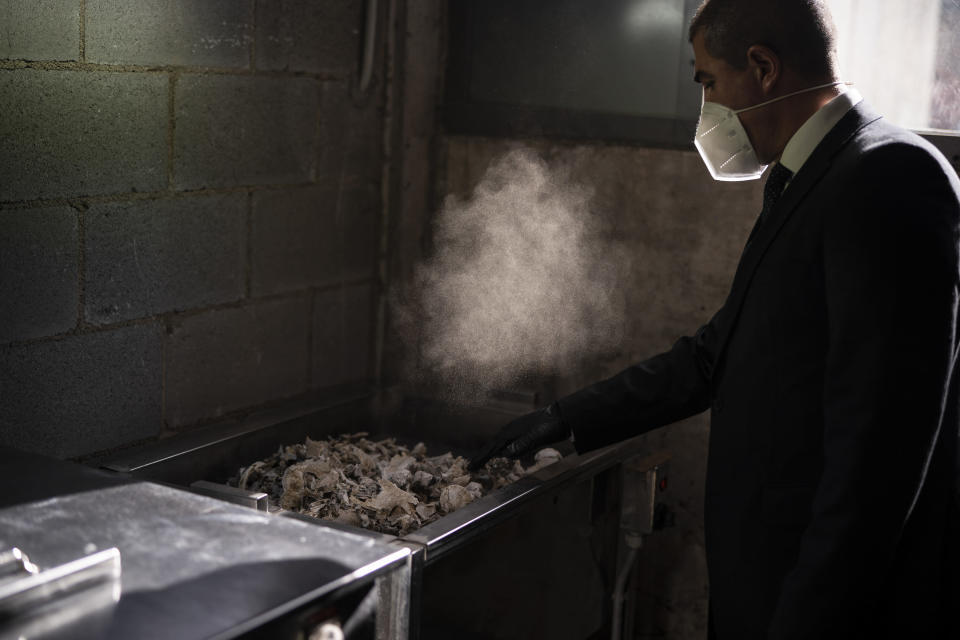 A mortuary worker collects the ashes of a COVID-19 victim from an oven after the remains where cremated at Memora mortuary in Girona, Spain, Nov. 19, 2020. The image was part of a series by Associated Press photographer Emilio Morenatti that won the 2021 Pulitzer Prize for feature photography. (AP Photo/Emilio Morenatti)
