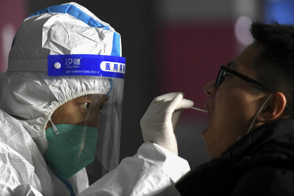 In this photo released by Xinhua News Agency, a medical staff in a protective suit takes a swab from a resident at a community center in Shijiazhuang in north China's Hebei province on Wednesday, Jan. 6, 2021. Lockdown measures were being imposed in a northern Chinese province where coronavirus cases more than doubled in the region near Beijing that's due to host some events in next year's Winter Olympics. (Wang Xiao/Xinhua via AP)