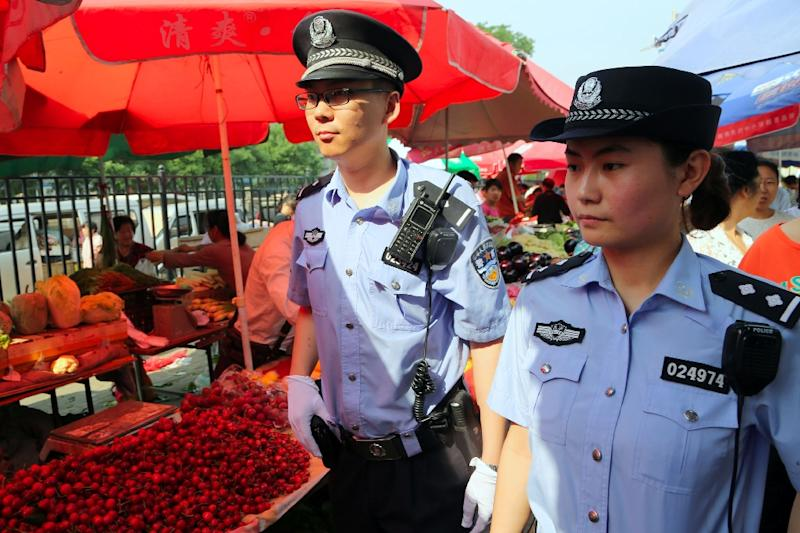 Armed police patrol a market in Urumqi, in northwest China's Xinjiang region, after a fatal attack in May 2014 (AFP Photo/STR)