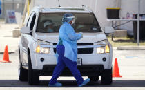 Medical personnel administer COVID-19 testing at a drive-thru site, Friday, Aug. 14, 2020, in San Antonio. Coronavirus testing in Texas has dropped significantly, mirroring nationwide trends, just as schools reopen and football teams charge ahead with plans to play. (AP Photo/Eric Gay)