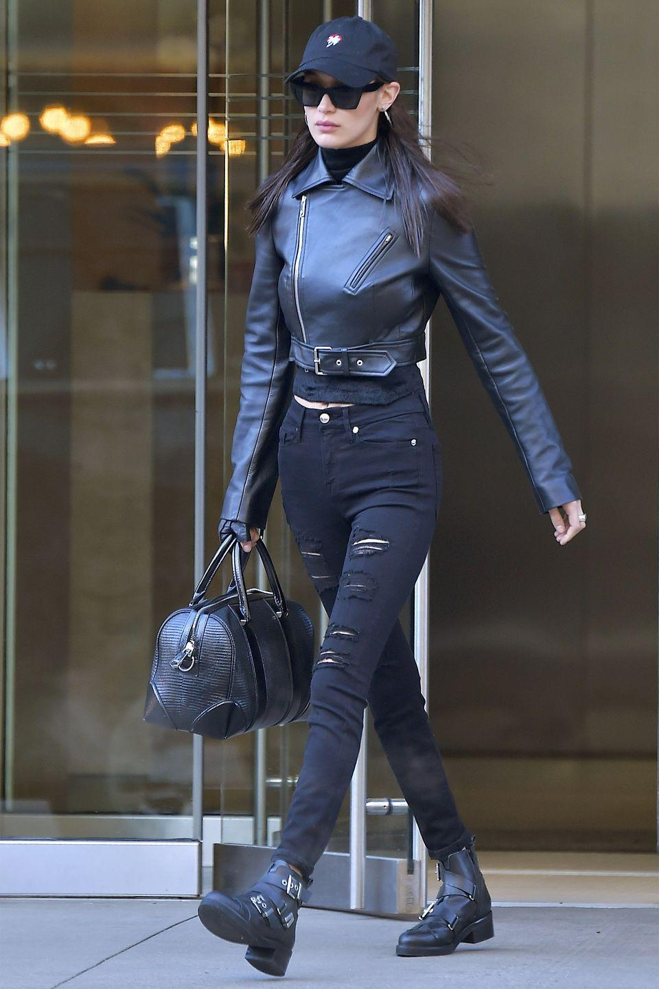 <p>In a black leather jacket, turtleneck, distressed Good American jeans, buckled ankle boots, mini duffle bag, sunglasses and dad hat while out in New York City.</p>