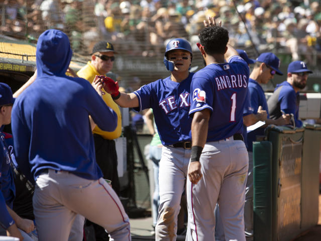 Texas Rangers' Shin-Soo Choo, center, is greeted by his teammates after scoring on a single by Danny Santana during the fourth inning of a baseball game against the Oakland Athletics, Sunday, Sept. 22, 2019, in Oakland, Calif. (AP Photo/D. Ross Cameron)