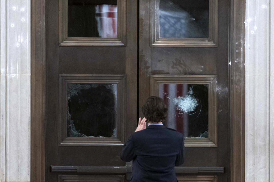 A man takes a photo of broken windows near the Rotunda in the early morning hours of Thursday, Jan. 7, 2021, after protesters stormed the Capitol in Washington, on Wednesday. (AP Photo/Andrew Harnik)