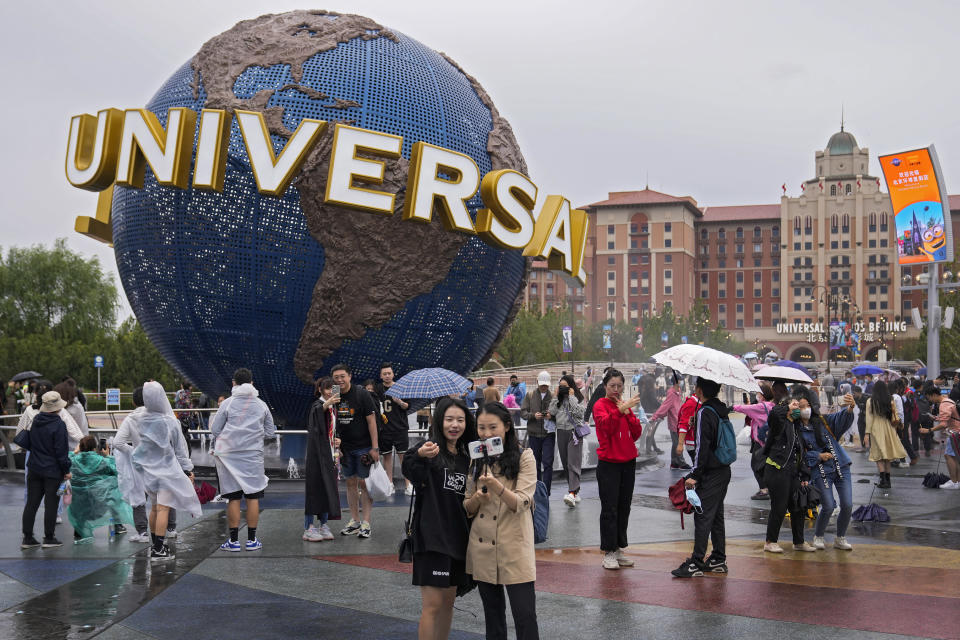 People take selfies with an icon near the entrance to Universal Studios Beijing in Beijing, Monday, Sept. 20, 2021. Thousands of people brave the rain visit to the newest location of the global brand of theme parks which officially opens on Monday. (AP Photo/Andy Wong)
