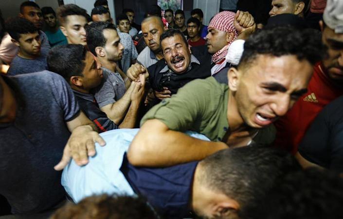 Palestinian relatives react as they arrive at the morgue of the al-Shifa hospital in Gaza City where the body of Mohammed Badwan was brought after he was shot dead by Israeli forces during protests along the border east of Gaza City on July 20, 2018 (AFP Photo/ANAS BABA)