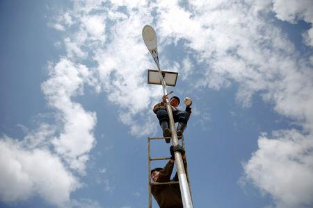 FILE PHOTO: A man paints a solar street lamp in the suburbs of Pyongyang, North Korea May 4, 2016. REUTERS/Damir Sagolj/File Photo