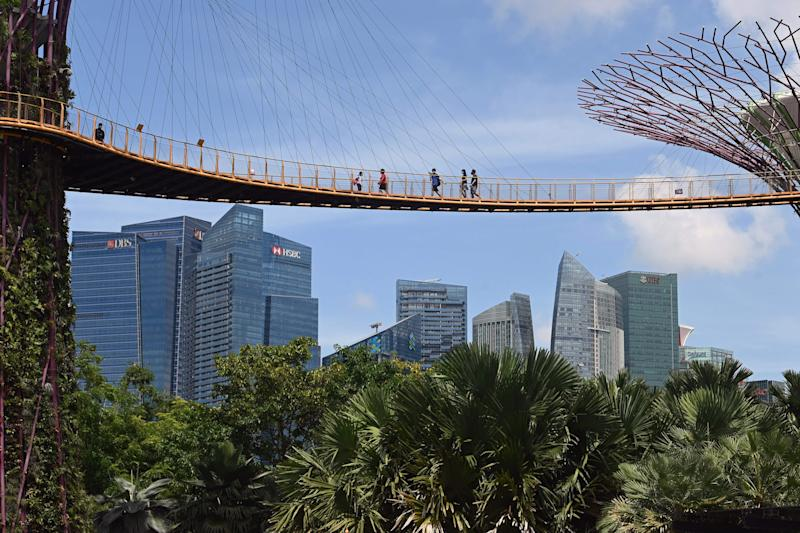 Visitors walk across the Supertree Grove skyway at Gardens by the Bay in Singapore on September 9, 2020, after the popular tourist attraction was reopened to the public on September 7 following closures due to restrictions to halt the spread of the COVID-19 coronavirus. (Photo by ROSLAN RAHMAN / AFP) (Photo by ROSLAN RAHMAN/AFP via Getty Images)