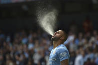 Manchester City's Kyle Walker blows water before the start of the English Premier League soccer match between Manchester City and Arsenal at Etihad stadium in Manchester, England, Saturday, Aug. 28, 2021. (AP Photo/Rui Vieira)