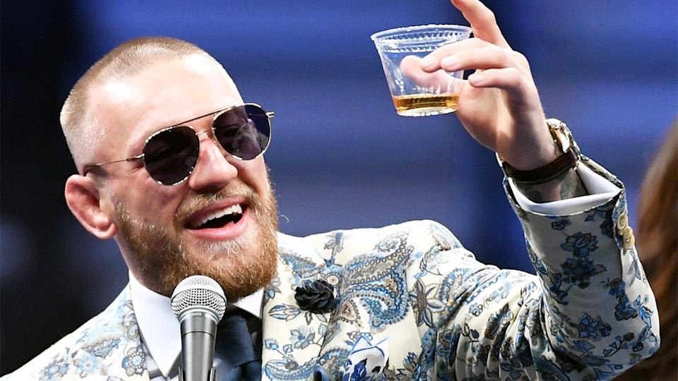 Conor McGregor (pictured) holding up a cup of Proper No. Twelve whiskey.
