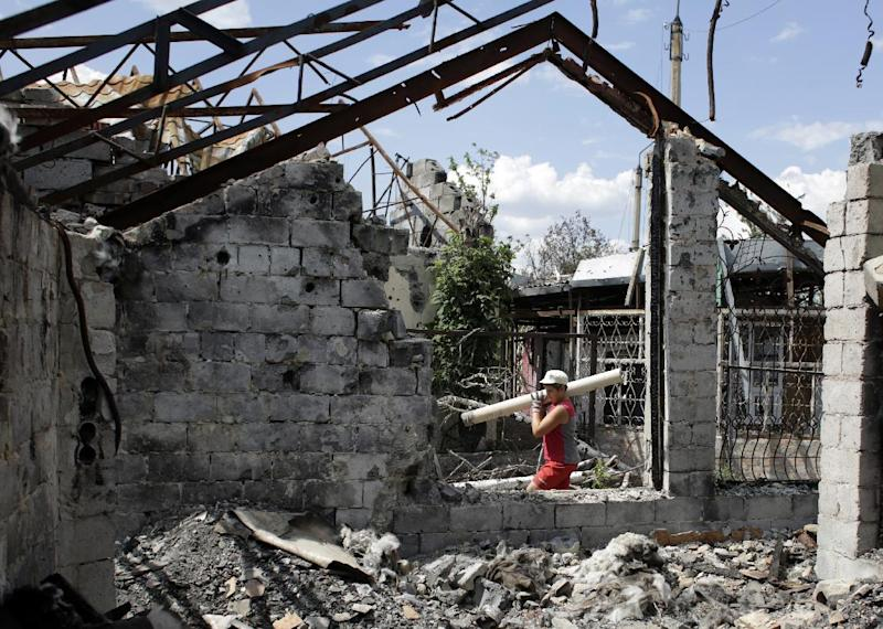 A man removes debris from a cafe which was destroyed during clashes between Ukrainian forces and pro-Russian militants, in the eastern city of Slavyansk, in the region of Donetsk, on August 5, 2014 (AFP Photo/Anatolii Stepanov)