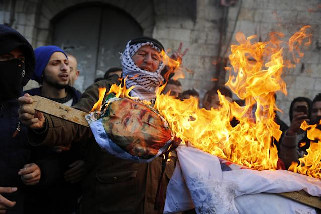 <p>Palestinian protesters burn an effigy of US President Donald Trump following his decision to recognize Jerusalem as the capital of Israel, in the West Bank city of Nablus, on Dec. 7, 2017. (Photo: Jaafar Ashtiyeh/AFP/Getty Images) </p>