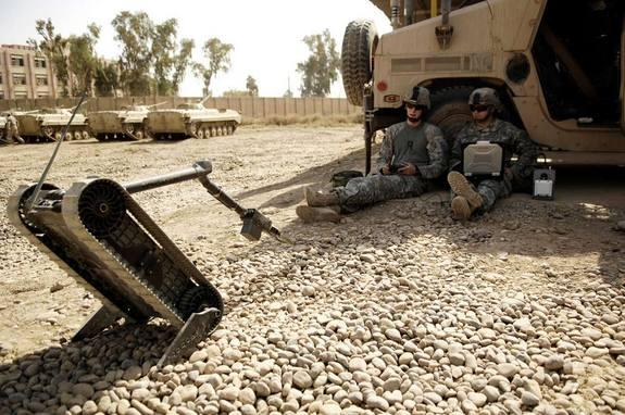 U.S. Army Jon Bridges, a native of Spring Creek, NY., teaches U.S. Army Staff Sgt. Aaron Wilwerding, a native of Kansas City, Mo., how to operate a Pack Robot at Forward Operating Base Base Hawk, Iraq on Sep. 18, 2008. Rigid robots such as thes
