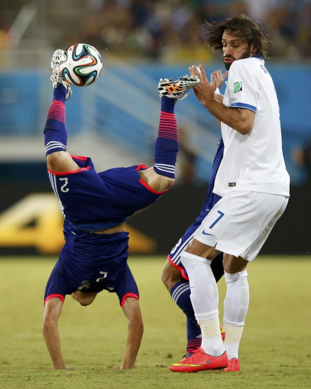Greece's Giorgios Samaras commits a foul against Japan's Atsuto Uchida (L) during their 2014 World Cup Group C soccer match at the Dunas arena in Natal June 19, 2014. REUTERS/Toru Hanai (BRAZIL - Tags: SOCCER SPORT WORLD CUP)