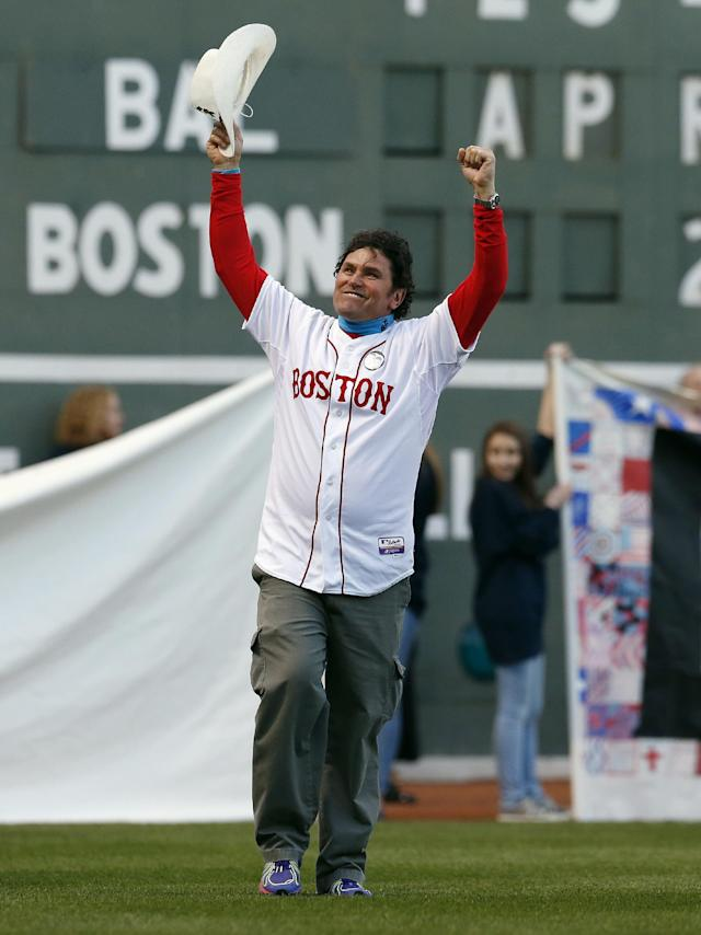 Boston Marathon bombing hero Carlos Arredondo waves to the crowd as he walks onto the field at Fenway Park during ceremonies marking the one-year anniversary of the bombing before a baseball game between the Boston Red Sox and the Baltimore Orioles in Boston, Sunday, April 20, 2014. (AP Photo/Michael Dwyer)