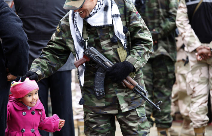 A member of the Libyan security forces pats the head of a little girl during the celebration of the second anniversary of the Libyan revolution in Benghazi, Libya, Sunday, Feb, 17, 2013. Libya's interim President Mohammed el-Megarif called on Sunday for unity in the North African nation as it celebrates the second anniversary of the uprising that toppled longtime dictator Moammar Gadhafi but plunged the country into lawlessness and economic woes. (AP Photo/Mohammad Hannon)