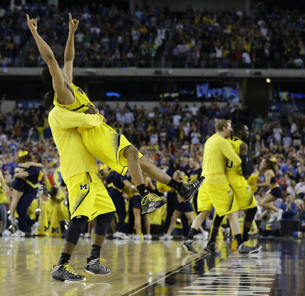 Michigan's Trey Burke, second from left, is lifted by Corey Person after beating Kansas 87-85 in overtime of a regional semifinal game in the NCAA college basketball tournament, Friday, March 29, 2013, in Arlington, Texas.(AP Photo/Tony Gutierrez)