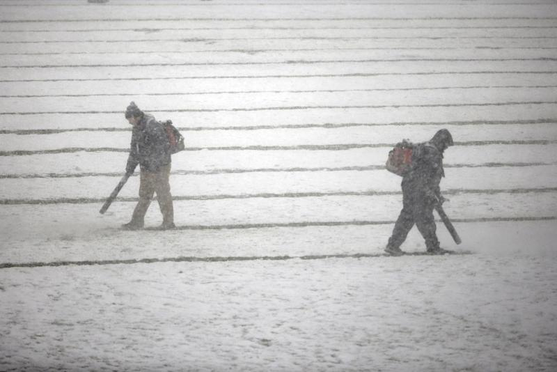 Philadelphia Eagles personnel clear snow before an NFL football game between the Philadelphia Eagles and the Detroit Lions, Sunday, Dec. 8, 2013, in Philadelphia. (AP Photo/Matt Rourke)