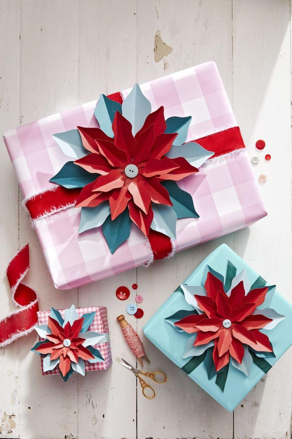 """<p>How gorgeous are those cardstock poinsettias? Not only are they a fabulous gift topper, but they look just as pretty all on their own. Bring them to life by cutting cardstock by hand (find the <a href=""""https://www.countryliving.com/diy-crafts/how-to/a3266/christmas-craft-templates/"""" rel=""""nofollow noopener"""" target=""""_blank"""" data-ylk=""""slk:template"""" class=""""link rapid-noclick-resp"""">template</a> here), then secure with a button and finish with a fringed ribbon.</p><p><a class=""""link rapid-noclick-resp"""" href=""""https://www.amazon.com/Neenah-Creative-Collection-Specialty-Cardstock/dp/B003A2I4V2?tag=syn-yahoo-20&ascsubtag=%5Bartid%7C10050.g.645%5Bsrc%7Cyahoo-us"""" rel=""""nofollow noopener"""" target=""""_blank"""" data-ylk=""""slk:SHOP CARDSTOCK"""">SHOP CARDSTOCK</a></p>"""