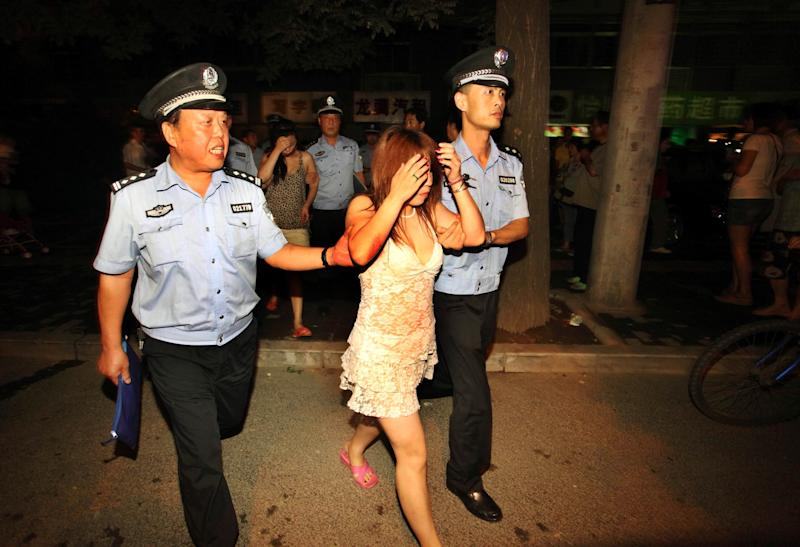 In this Aug. 13, 2010 photo, policemen detain suspected prostitutes in a campaign to crack down on prostitution in Xi'an, in northwestern China's Shaanxi province. Police in China frequently beat, torture and arbitrarily detain suspected sex workers, often with little or no evidence that they engaged in prostitution, Human Rights Watch said in a report Tuesday, May 14, 2013, calling on the government to discipline abusive officers. (AP Photo) CHINA OUT