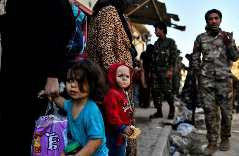 A Syrian child looks on as civilians gather in western Raqa after fleeing fighting between US-backed forces and the Islamic State group on October 12, 2017