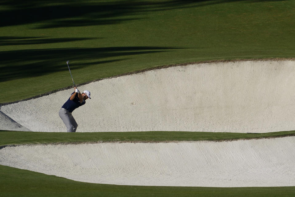 Dustin Johnson hits out of a bunker on the eighth hole during the second round of the Masters golf tournament Friday, Nov. 13, 2020, in Augusta, Ga. (AP Photo/David J. Phillip)