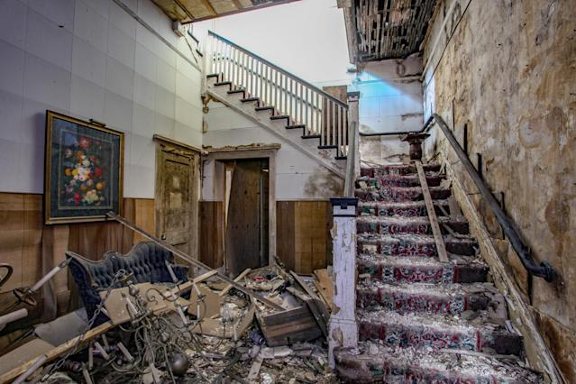<p><span>Black mold has engulfed the walls, and chipped tiles from the collapsed ceilings cover many of the floors of the Moulton and Kyle Funeral Home in Jacksonville, Fla. </span>(Photo: Caters News) </p>