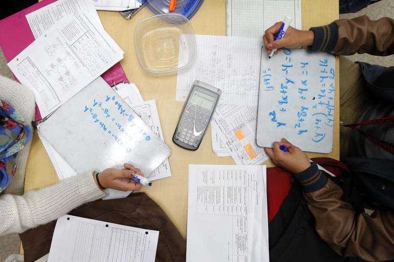 """Students solve problems in Crystal Kirch's pre-calculus class at Segerstrom High School in Santa Ana, Calif., Wednesday, Jan. 16, 2013. A growing number of teachers are implementing what is known as """"flipped learning,"""" in which students learn lessons as homework, mostly through online videos produced by teachers, and use classroom time to practice what they learned. (AP Photo/Jae C. Hong)"""