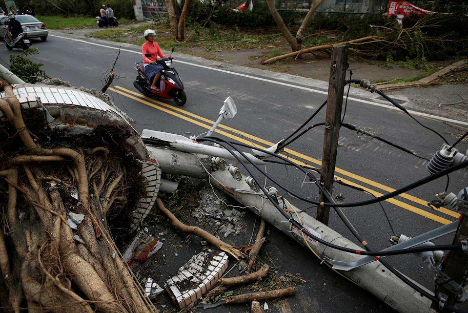 <p>A motorcyclists ride past a fallen utility pole and trees damaged by Typhoon Nepartak, in Taitung, Taiwan July 9, 2016. (Photo: Tyrone Siu/REUTERS) </p>
