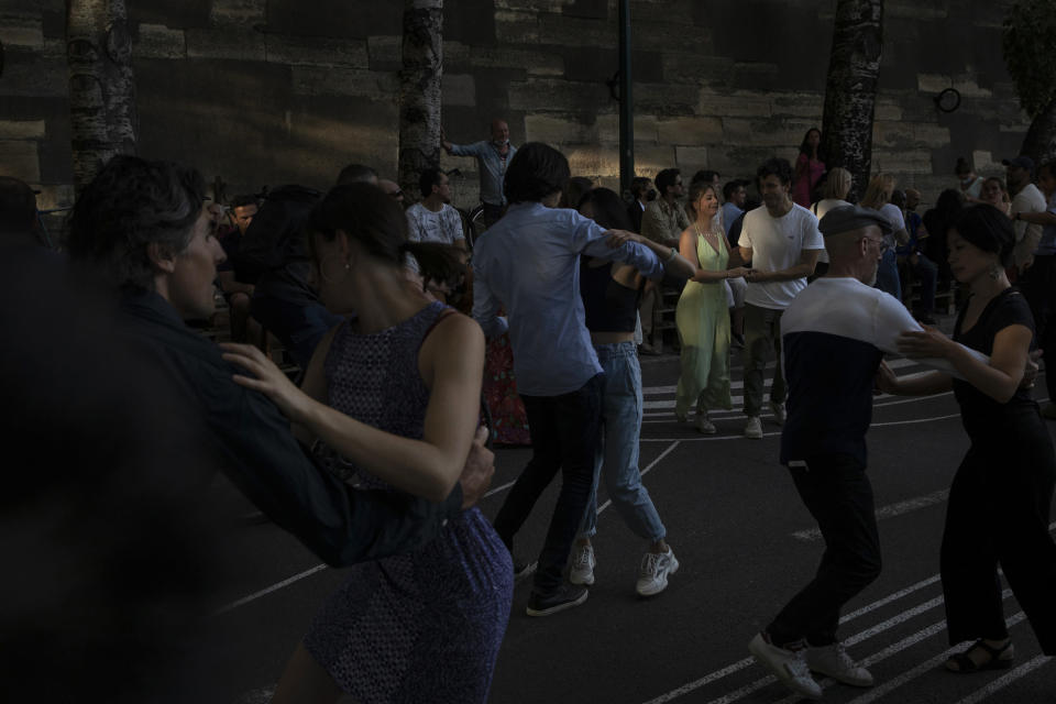 People dance swing on the rhythms of a live band by the restaurant Le Marcounet, in Paris, Sunday, Aug. 1, 2021. The sanitary pass, which proves someone has been vaccinated or recently done a test or recovered from Covid-19, will be mandatory in bars and restaurants, cultural venues of more than 50 people, museums, shopping malls and for long distance travels. (AP Photo/Adrienne Surprenant)