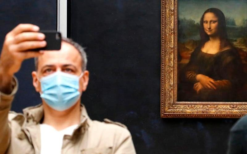 A visitor to the Louvre has plenty of room to take a selfie with Mona Lisa. CREDIT: AFP - FRANCOIS GUILLOT /AFP