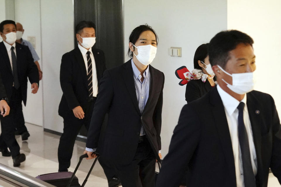 Kei Komuro, center, fiance of Japan's Princess Mako, is escorted by security personnel as he leaves the Narita International Airport in Narita, near Tokyo, Monday, Sept. 27, 2021, after returning to Japan from the United States. (AP Photo/Eugene Hoshiko)