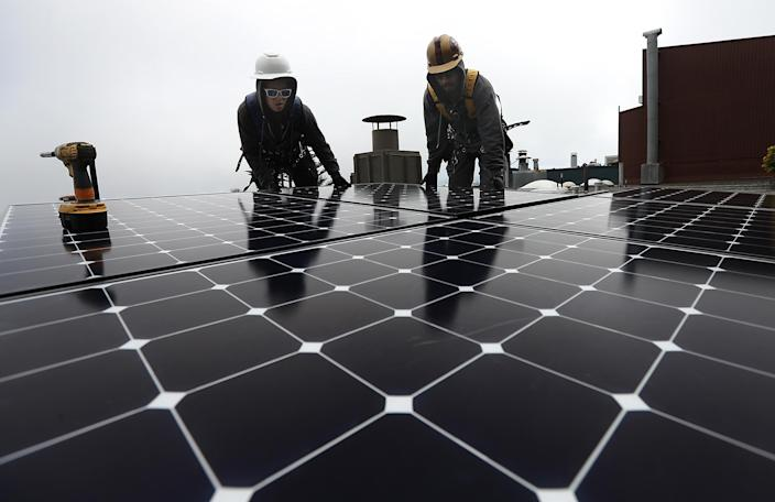 Workers install solar panels on the roof of a home in San Francisco on May 9. (Photo: Justin Sullivan/Getty Images)