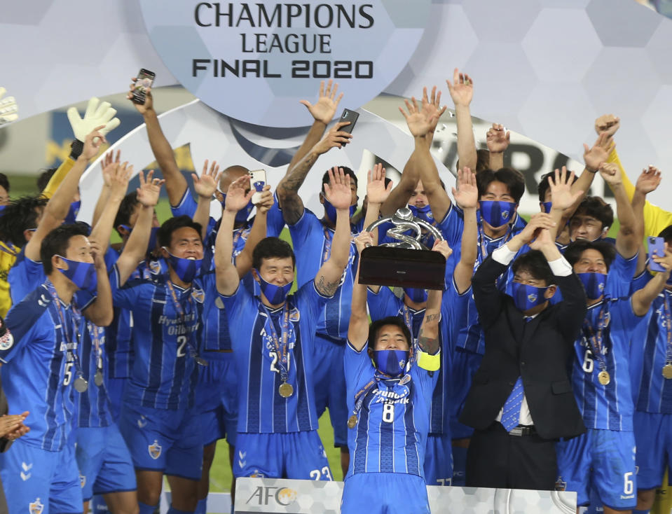 Ulsan Hyundai's players celebrate with a trophy after the AFC Champions League final match against Persepolis in Al Wakrah, Qatar, Saturday, Dec. 19, 2020. (AP Photo/Hussein Sayed)