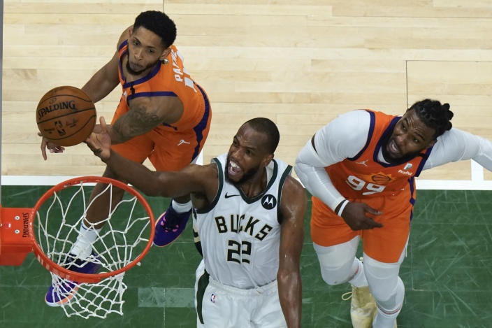 Milwaukee Bucks forward Khris Middleton (22) drives to the basket against Phoenix Suns guard Cameron Payne, left, and Jae Crowder, right, during Game 4 of basketball's NBA Finals in Milwaukee, Wednesday, July 14, 2021. (AP Photo/Paul Sancya, Pool)
