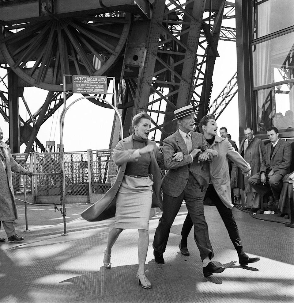 <p>Audrey Hepburn and Fred Astaire, along with costar Kay Thompson, dance through the Eiffel Tower while shooting <em>Funny Face </em>in 1956. Hepburn did all her own singing for the musical.</p>