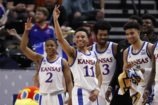 Kansas guard Charlie Moore (2), guard Devon Dotson (11), guard K.J. Lawson (13) and the rest of their bench celebrate a 3-pointer against Northeastern during the second half of a first-round game in the NCAA mens college basketball tournament Thursday, March 21, 2019, in Salt Lake City. (AP Photo/Jeff Swinger)