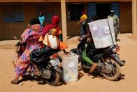 Electoral workers transport ballot boxes on their motorcycles as they arrive to prepare a polling station ahead of the presidential and legislative elections, in Ouagadougou,