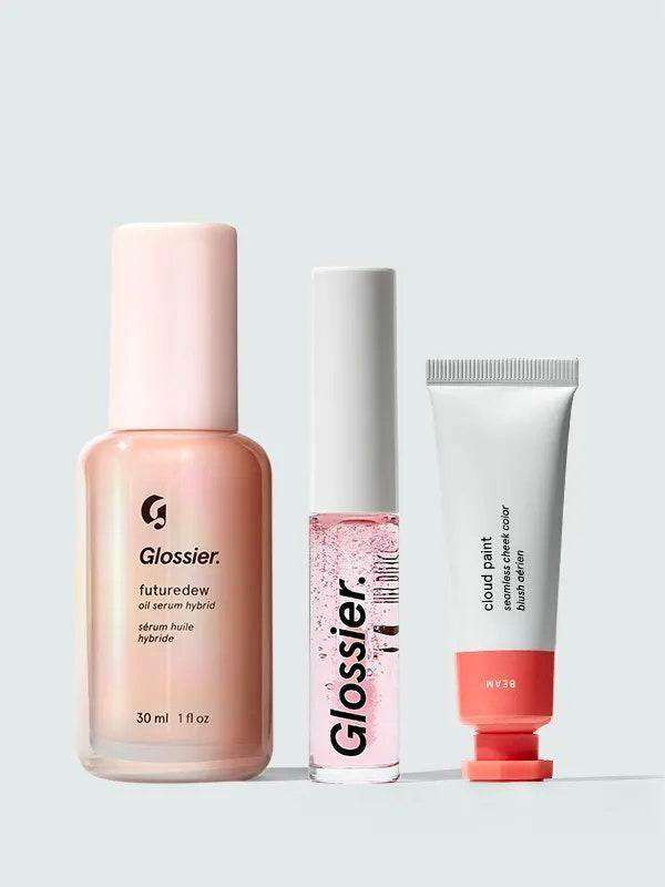 """Here's a gift set that's actually worth your money. Glossier's Dewy Skin bundle comes with three full-size products—its Futuredew oil serum, Cloud Paint lip-and-cheek duo, and Lip Gloss. Oh, and you can pick the shades you think she'll like most, so you're not stuck gifting a random mix of colors. $56, Glossier. <a href=""""https://www.glossier.com/products/the-dewy-look"""" rel=""""nofollow noopener"""" target=""""_blank"""" data-ylk=""""slk:Get it now!"""" class=""""link rapid-noclick-resp"""">Get it now!</a>"""