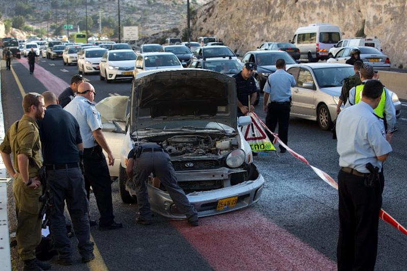 Israeli police inspect the damaged car of a Palestinian woman after she detonated a small bomb on the highway leading from the Jewish settlement of Maale Adumim to Jerusalem, on October 11, 2015 (AFP Photo/Menahem Kahana)